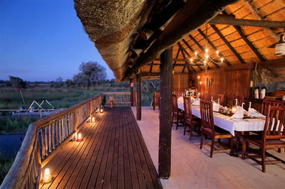 Dining area and verandah with view at Gunn's Camp, Okavango Delta